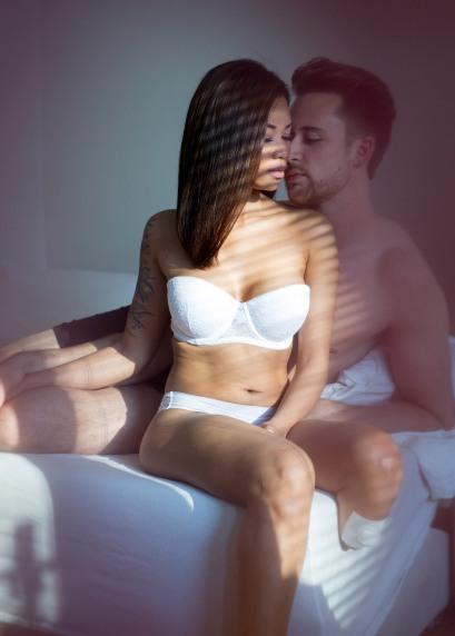 En kvinne i 20-årene med asiatisk utseende sitter på sengekanten. Hun har mørkt hår, er slank og har en tatovering ned langs den høyre overarmen. Hun har på seg en hvit truse og BH uten stropper. Venstrefoten er amputert under kneet, og ved amputasjonsområdet har hun et hvitt plaster. En hvit mann i 20-årene ligger bak henne. Han har på seg boksershorts, støtter seg med albuen og har ansiktet sitt kjært inntil kvinnens kinn. Begge har lukkede øyne. Sola skinner inn i rommet på paret. Skygger fra persienner danner mørke striper på kroppene.