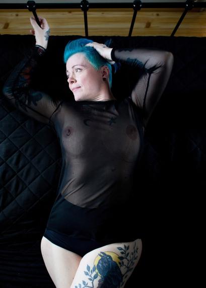 En middelaldrende kvinne ligger på ryggen i en sort seng. Kvinnen har turkist hår og en fyldig kropp. Brystene hennes er synlige gjennom en gjennomsiktig, sort, langermet topp. Den ene brystvorten er piercet. Hun har en sort truse på seg. Kvinnen har flere tatoveringer på kroppen. Øverst på høyre bryst har hun en halvmåne, og en stjerne på det venstre. Det venstre låret er tatovert med en ravn som sitter på en gren i måneskinn. Kvinnen drar den ene hånda gjennom håret sitt, og holder den andre fast på en av sengestolpene. Hodet er vendt mot den ene siden og hun har et åpent blikk.