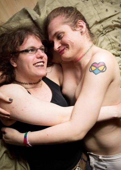 De to ligger tett sammen. De ligger på siden, vendt mot hverandre og med armene rundt hverandre. De ser på hverandre og smiler varmt.