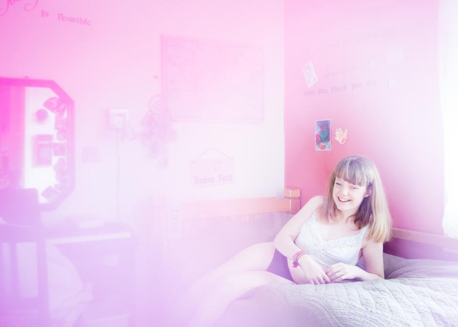 Jenta i tenårene sitter i senga og lener seg på venstre albue. På en hvit vegg ved siden av henne, henger det et skilt der det står «Drøm søtt». Framfor henne står en skrivepult. På veggen ved pulten henger det et speil med mange små, utklipte bilder festet ved ramma. Det er en tåket glød rundt jenta som smiler bredt.