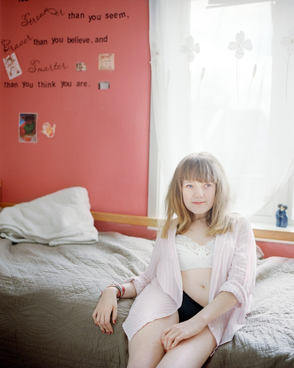 Jenta i tenårene sitter på sengekanten og smiler mildt i kamera. Hun har en lys rosa, ukneppet bluse utenpå en hvit BH med blonder, og sort truse. På en rosa vegg bak henne står det «Stronger than you seem, braver than you believe, and smarter than you think you are». Dagslyset skinner gjennom tynne, lyse gardiner framfor vinduet over senga.