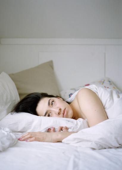 En ung kvinne i 20-årene ligger under dyna i en seng. Hun har langt, sort hår, brune øyne og fyldige lepper. Hun ligger på siden, hviler hodet på puta og ser tankefullt og alvorlig framfor seg.