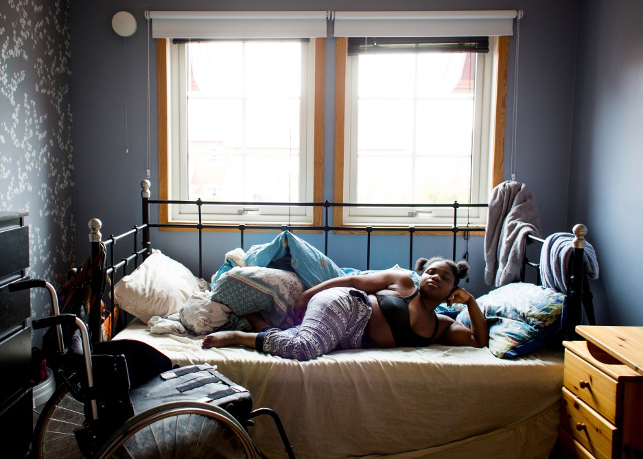 Den mørkhudete jenta ligger på siden i senga og poserer som en modell med hodet hevet mens hun støtter det til hånda. Hun ser rett i kamera med et bestemt blikk. Den ene foten ligger med elegant bøy i kneleddet over den andre. Jenta har sort BH og pysjbukse på seg. Et par dyner ligger uryddig rundt henne i senga, det er puter i begge ender av den. På det ene gitteret i sengeenden henger det to håndklær. På gulvet ved siden av senga står en rullestol. Rommet er malt grått og den ene veggen har en grå tapet med hvite blomster.