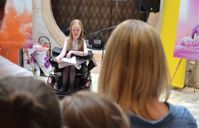 På bildet ser man en ung kvinne i rullestol snakke inn i en mikrofon. I forgrunnen av bildet ser man bakhodet på flere mennesker. I bakgrunnen står to av bildene fra fotoutstillingen.