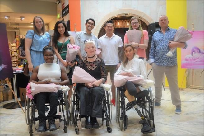 På bildet ser man prosjektleder, fotograf og syv av deltakerne smile til kameraet.