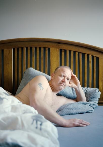 En middelaldrende mann ligger i en seng med dyna over underkroppen, og støtter hodet i venstre hånd. Han har kort, grått hår med høyt feste, blå øyne, tredagersskjegg, og en tatovering av en rose på sin høyre overarm. Han ser i kamera med et alvorlig, tankefullt uttrykk.